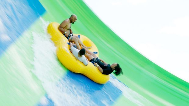 Thrillseekers ride the Gravity Wave water slide at Funfields theme park in Whittlesea on Tuesday.
