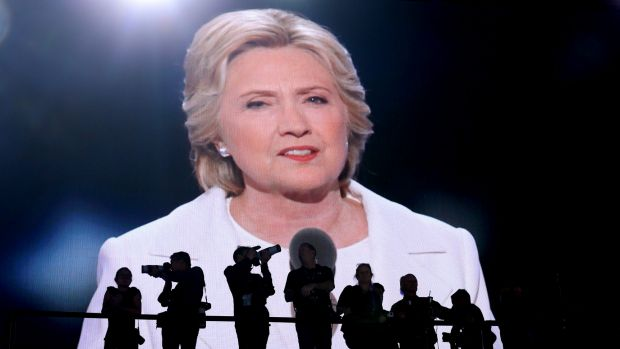 Photographers stand as Hillary Clinton, 2016 Democratic presidential nominee, is seen speaking on a screen during the ...