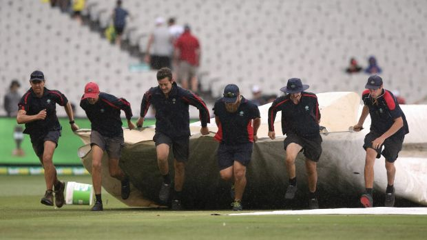 Run for cover: Rain on day four squandered hope of an English victory in Melbourne.