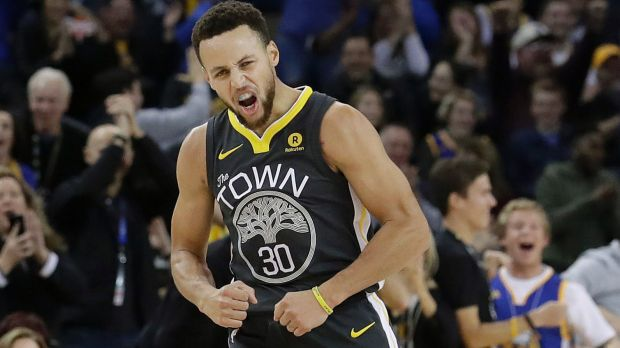 Golden State Warriors guard Stephen Curry reacts after scoring during the first half of the team's NBA basketball game ...