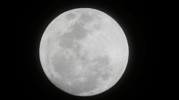 The moon appears in the first supermoon of 2018 as seen from suburban Makati city east of Manila, Philippines, on ...