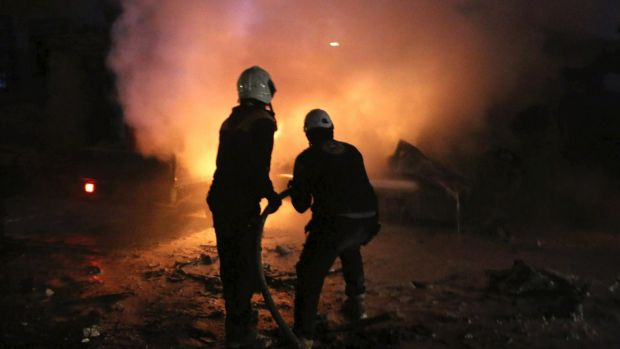 Syrian White Helmet civil defence workers extinguishing a fire following a bombing that targeted the office of Ajnad ...