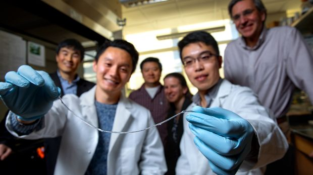 Alan Chiu, left, and Duo An hold a sample of the TRAFFIC  implant. In the background are researchers Minglin Ma, Dan ...