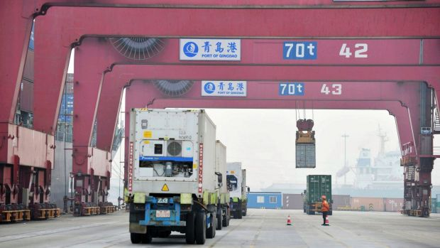 Cargo trucks move through a shipping port in Qingdao in eastern China's Shandong province.