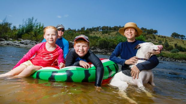 Cameron and Sarah-Jane Aitken from Ainslie cooled down from Friday's 35 degree heat with their children Tomas (9) and ...