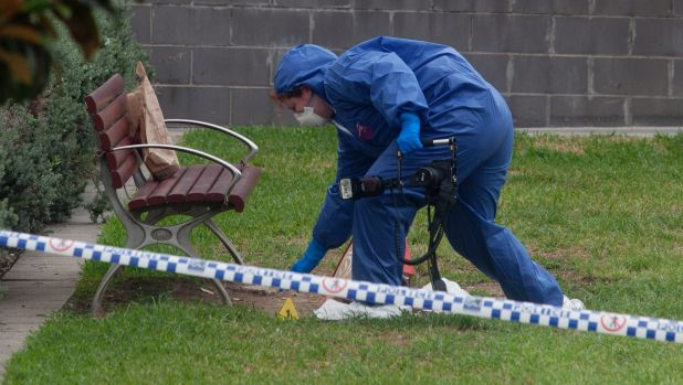 A forensics officer outside Hurstville train station, where a man was stabbed to death.
