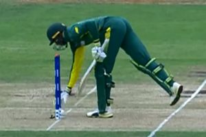 South Africa's Jiveshan Pillay picks the ball up to return it to the fielding side.