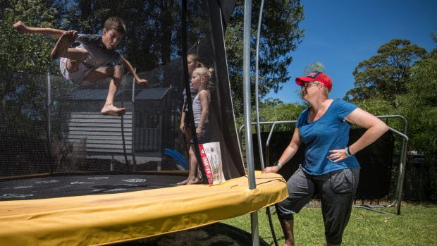 Dimity Statheos watches her children, Silas and Karis with neighbour Lydia, on their new trampoline with their old ...