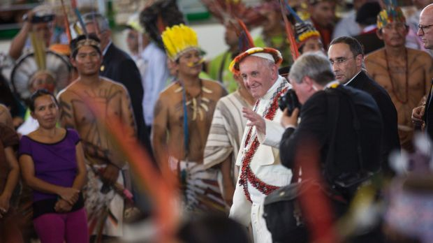 Wearing an indigenous headdress and jewelry, Pope Francis waves during a meeting with indigenous groups.