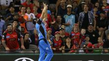 Ben Laughlin of the Strikers catches Dwayne Bravo of the Renegades near the boundary before throwing the ball to ...