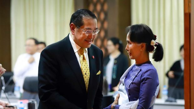 Myanmar's Foreign Minster and de facto leader Aung San Suu Kyi, right, shakes hands with Surakiart Sathirathai, left, a ...