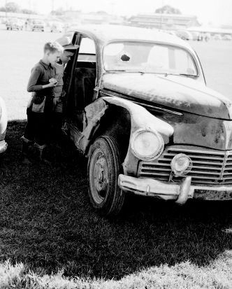 A couple of young locals check out a damaged car in Cairns.
