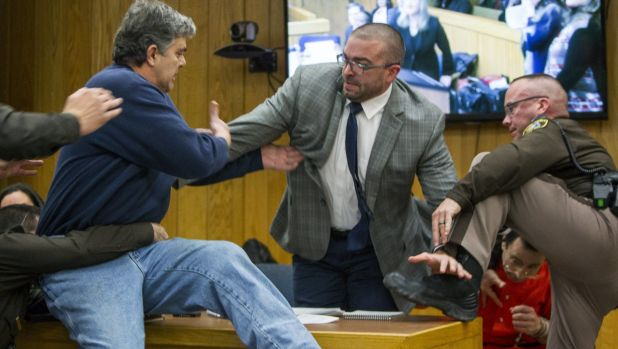 Randall Margraves, father of three victims of Larry Nassar , left, lunges at Nassar, bottom right, in court.