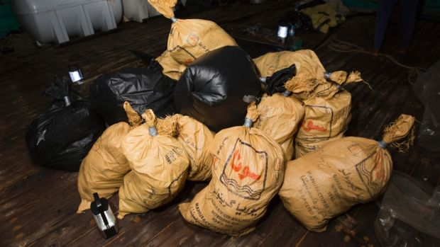 Parcels of narcotics seized by HMAS Warramunga lay on the deck of a smuggling vessel in the Middle East.