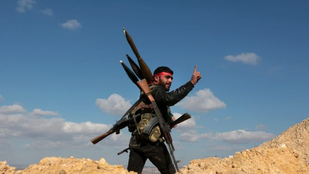 A pro-Turkey Syrian fighter waves on Bursayah hill, which separates the Kurdish-held enclave of Afrin from the ...