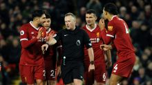 Referee Johnathan Moss awards the second penalty as Liverpool players react during the English Premier League soccer ...