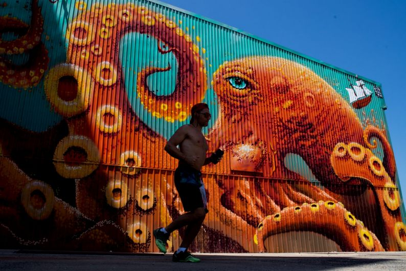 Modern Melbourne. A man jogs past a huge mural on the end of a boatshed on Northwharf.