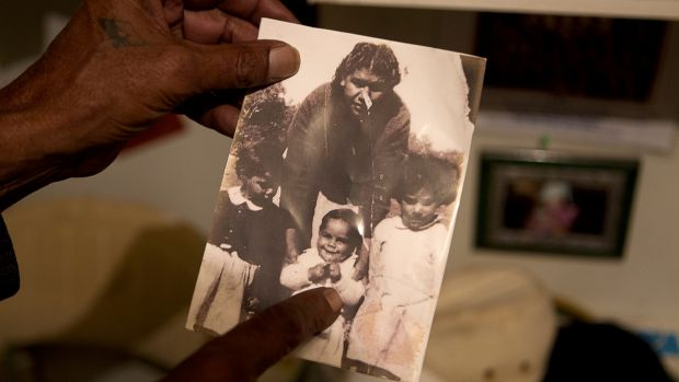 Kutcha Edwards holds a photo of himself as a child with his sisters, Maria and Alice, and cousin Mary Briggs, nee Edwards.