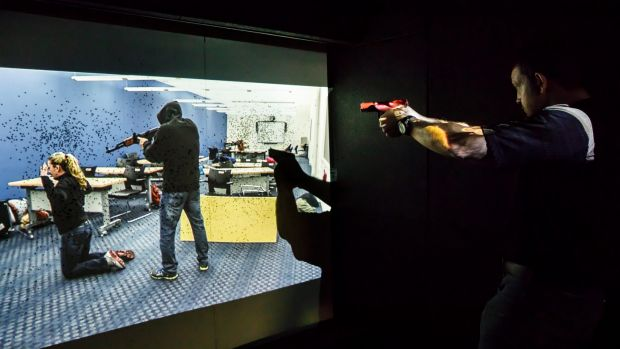 Paul Burns demonstrates the company's prototype mobile firing range, where police and soldiers must react to virtual ...