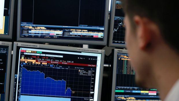 A currency trader watches monitors in a brokerage firm.
