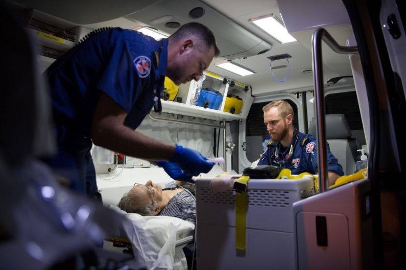 11:01pm. NSW Ambulance Paramedics Eugene Roser (left) and Gareth Garne work on a 70 year old male from Leichhardt who ...
