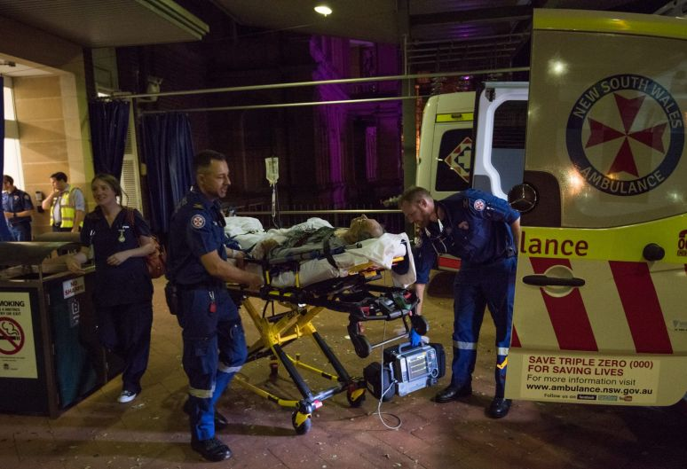 11:18pm. NSW Ambulance Paramedics Eugene Roser (left) and Gareth Garne transport a 70 year old male from Leichhardt, who ...