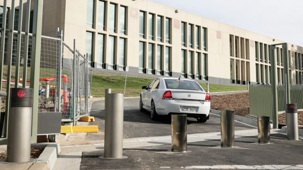 A Comcar enters the grounds of Parliament House by driving past drives past retractable bollards.