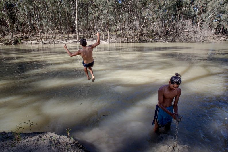 Family members swimming in the Murrumbidgee River. The Edwards Family were welcomed back onto their country by Elders of ...