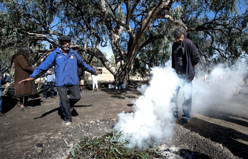 Mick and Arthur Edwards smoke themselves as part of the welcome back to country ceremony.