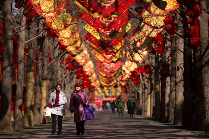 Woman walk along a pathway decorated for the Lunar New Year at a public park in Beijing. Chinese worldwide are preparing ...