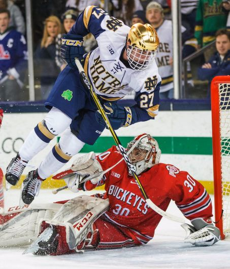 Notre Dame's Bobby Nardella (27) flips as he hits Ohio State's Sean Romeo (30) during an NCAA college hockey game in ...