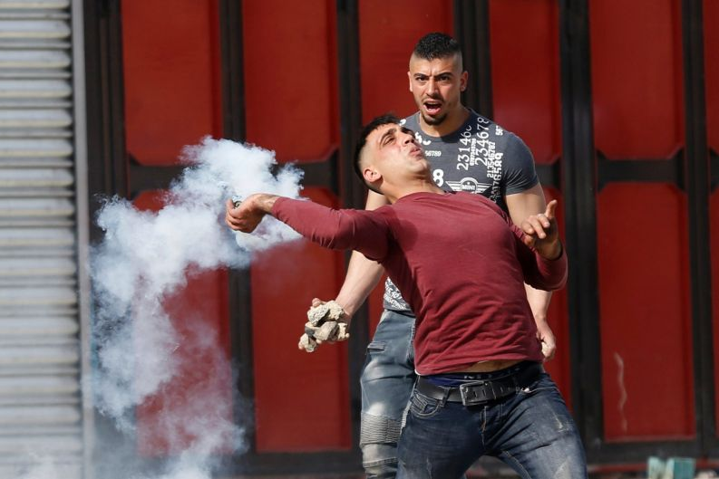 Palestinian demonstrator throws back a tear gas canister during clashes with Israeli troops following a demonstration in ...