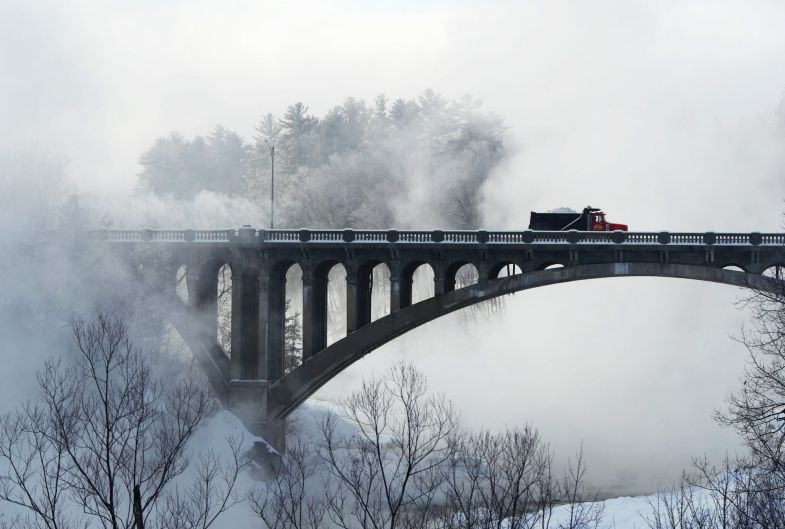 Freezing fog rises from the Androscoggin River as dump truck driver Jimmy Figer crosses the Memorial Bridge during snow ...