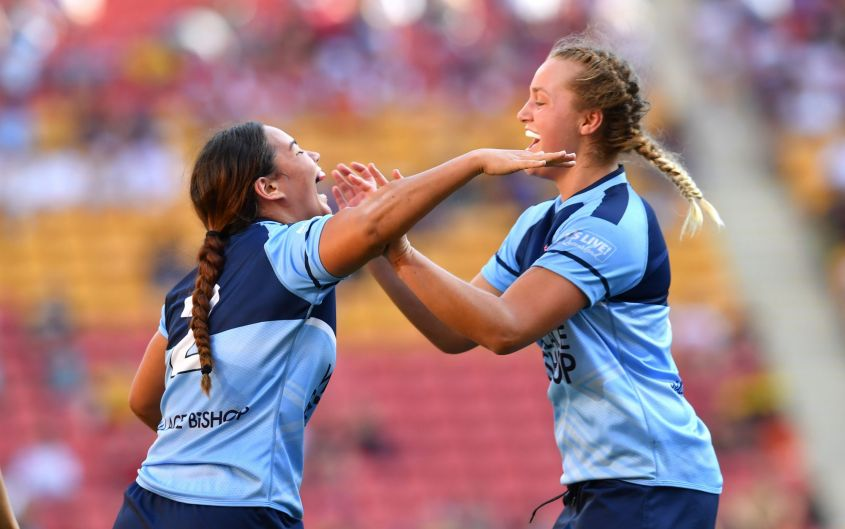Kennedy Cherrington  (left) of the Waratahs celebrates scoring a try with team mate Bella McKenzie (right) against the ...