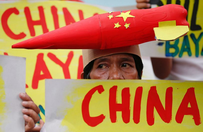 A protester wears a mock missile on her head during a rally at the Chinese Consulate to protest China's alleged ...