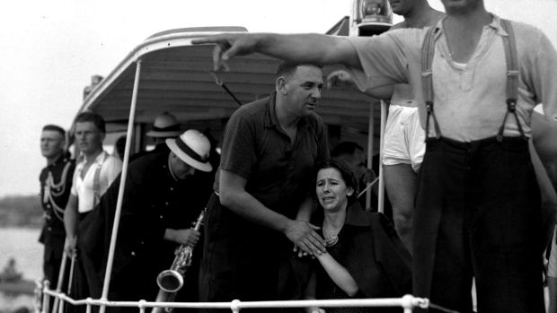 A woman is comforted on board the police launch Cambria.