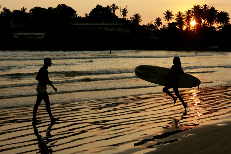 A tourist is silhouetted as she runs into the sea with a surfboard on Dewata Beach at sunset in Galle, Sri Lanka.
