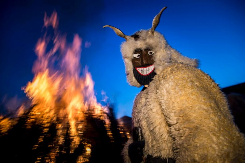 A reveller wearing a sheep wool costume with horns and a mask stands in front of a bonfire in Mohacs, some 210 kms south ...