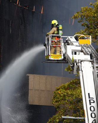 A firefighter pours water onto the burning construction site.