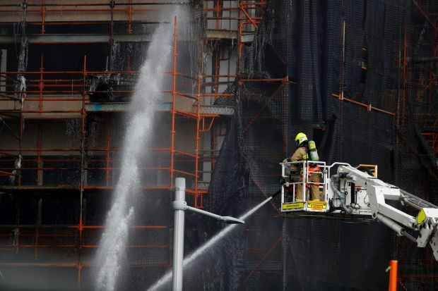 A firefighter pours water into the construction site after a fire broke out.