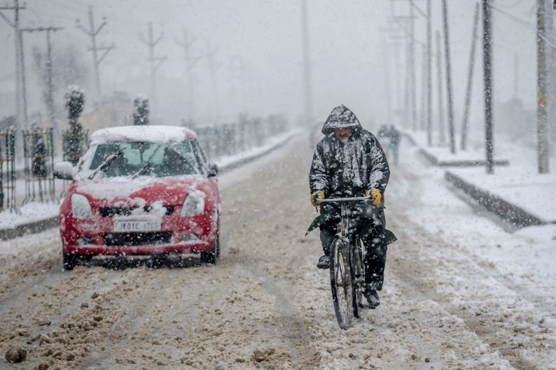 A cyclists rides through snowfall on the outskirts of Srinagar, Indian controlled Kashmir.