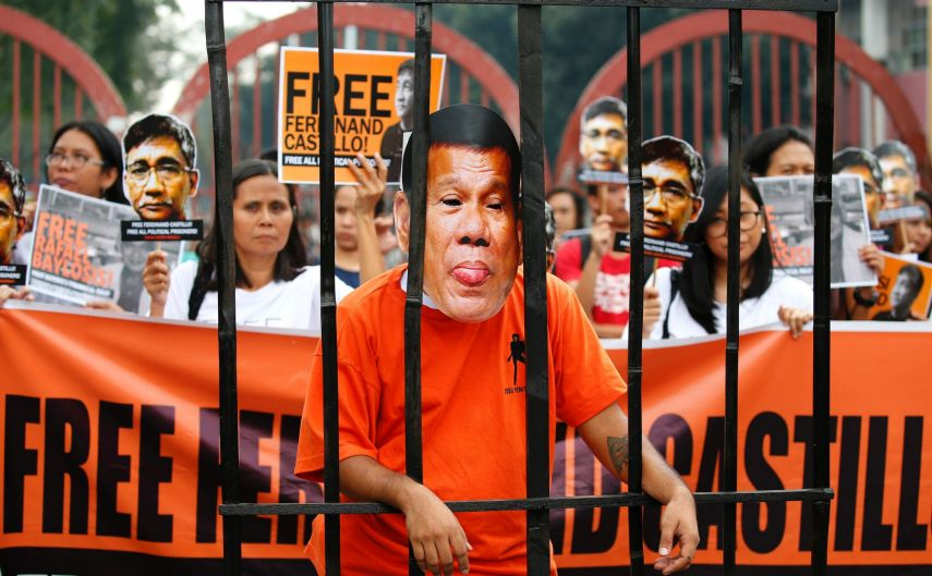 Protesters display cutouts of detained communist peace talks consultant Ferdinand Castillo behind a mock jail cell of ...