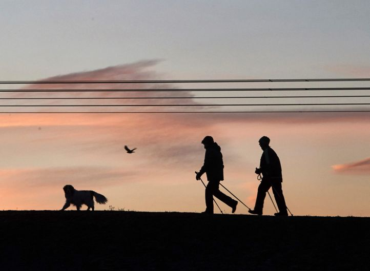 Two strollers and a dog walk during sunrise in Gelsenkirchen, western Germany.