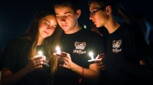 Attendees comfort each other at a candlelight vigil for the victims of the shooting at Marjory Stoneman Douglas High ...