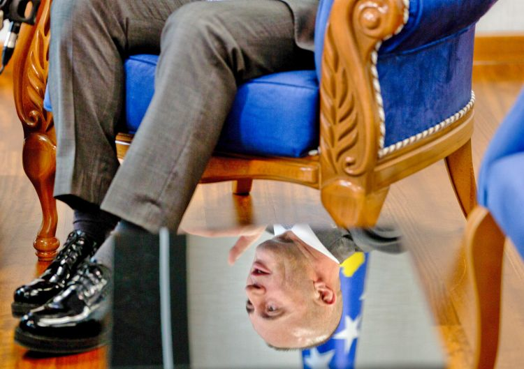 A reflection of Kosovo prime minister Ramush Haradinaj is seen on a table during an interview with The Associated Press ...