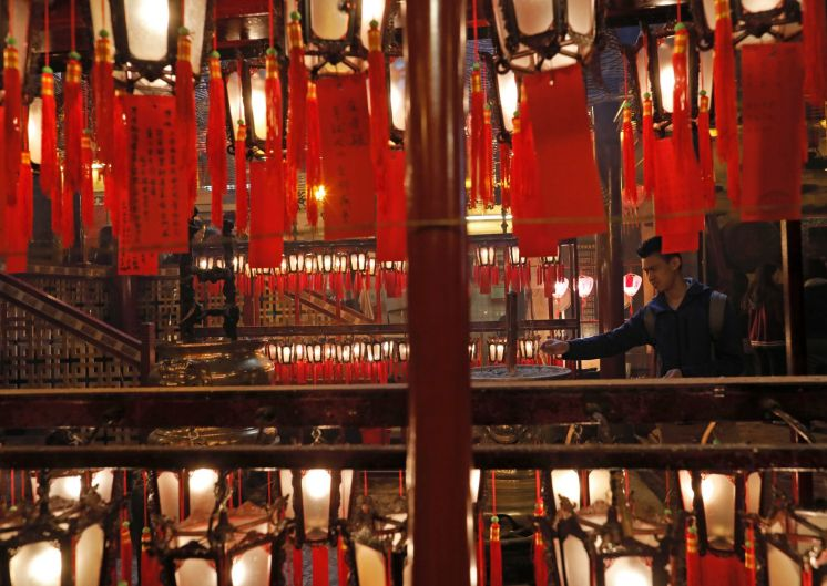 A man burns joss sticks as he prays at the Man Mo Miu Temple on the second day of the Lunar New Year in Hong Kong, ...