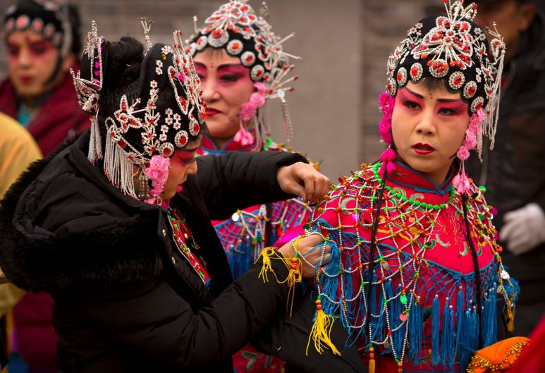Participants adjust their costumes before their performance during a temple fair to celebrate the Lunar New Year holiday ...
