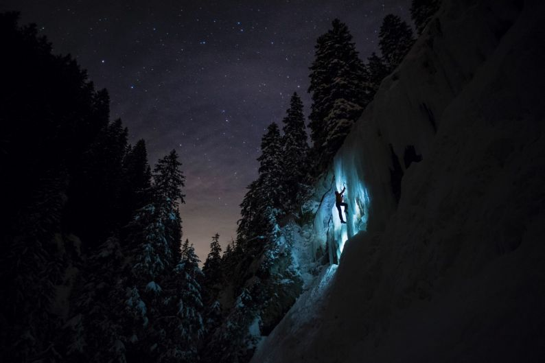 Pierre, a member of Team Arnicare, climbs an ice cascade during a night-time training session under a stary night near ...