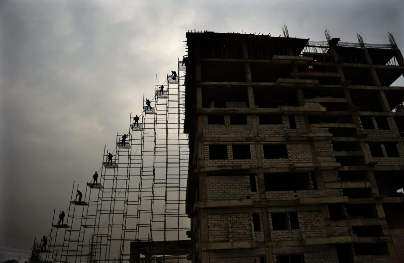 Laborers on scaffolding bring steel rods from the ground to the top of a building under construction in Greater Noida, ...