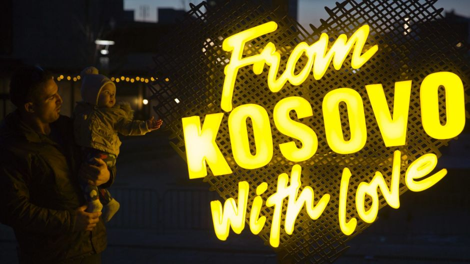 A father holds his baby as they pass by an illuminated writing decorating the main square in capital Pristina, Kosovo ...